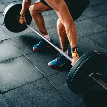 Man lifting barbell from floor