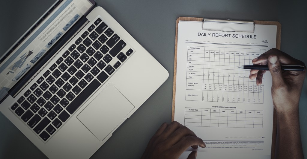 Filling out a daily schedule report with a pen